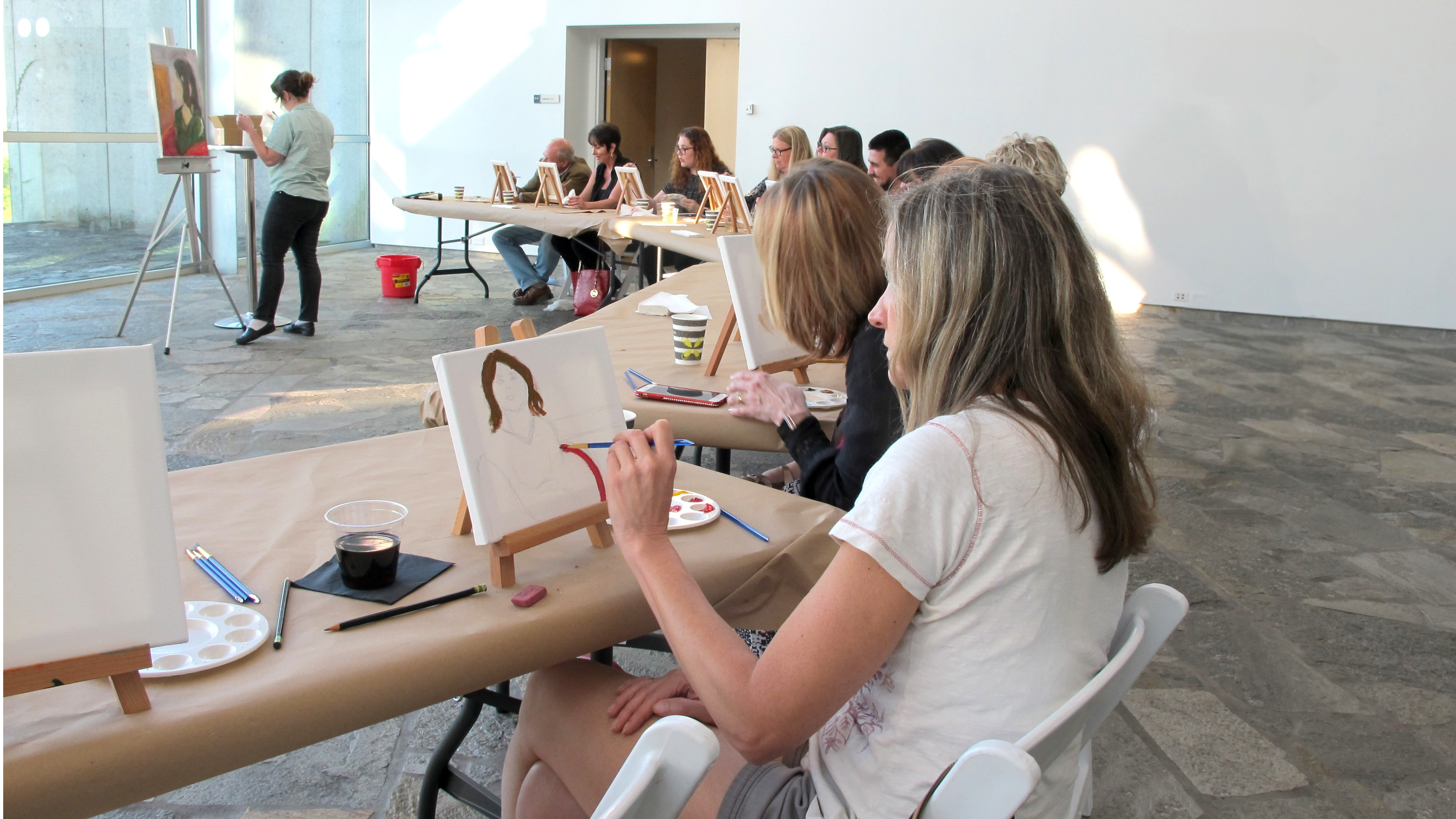 Woman sits at a long table and paints on a small canvas. Other painters sit at tables behind her.