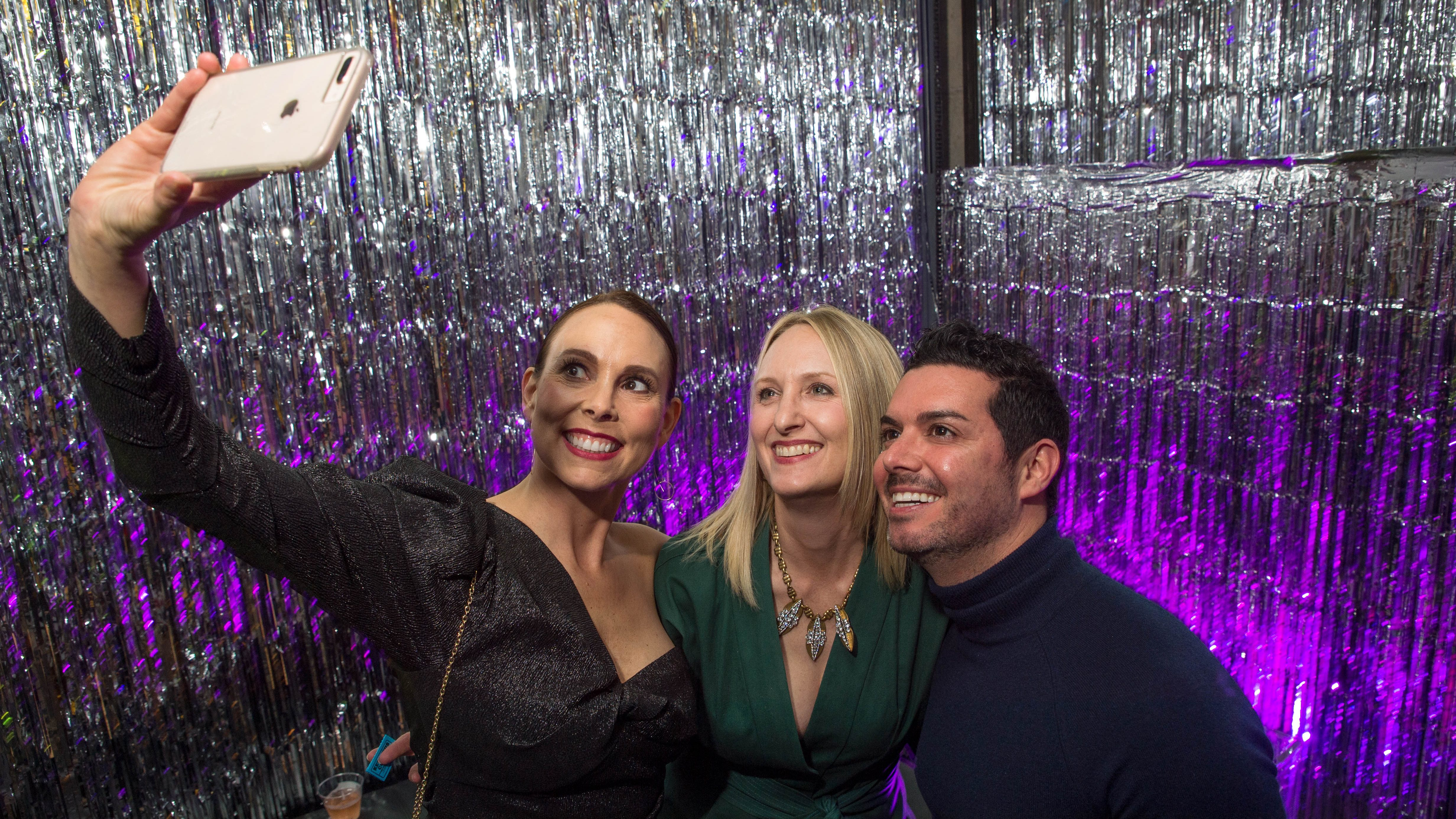 Two women and a man take a selfie against a shimmery silver background with purple lighting.