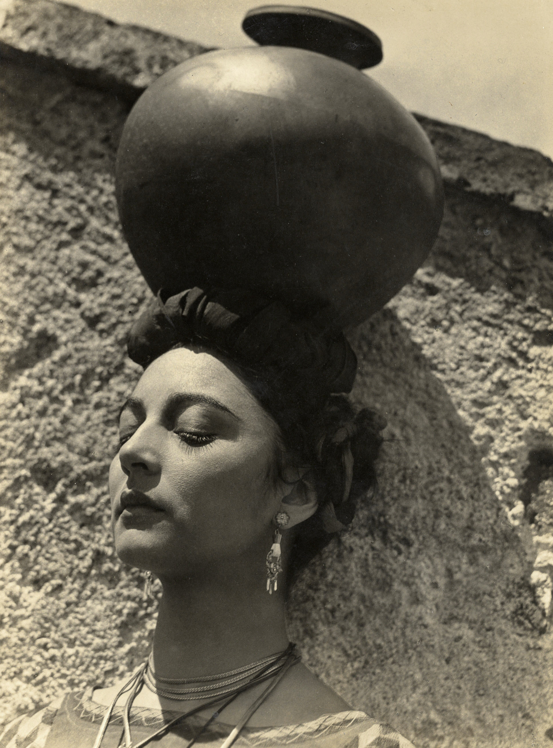 A woman with a clay pot on her head against a stucco wall.