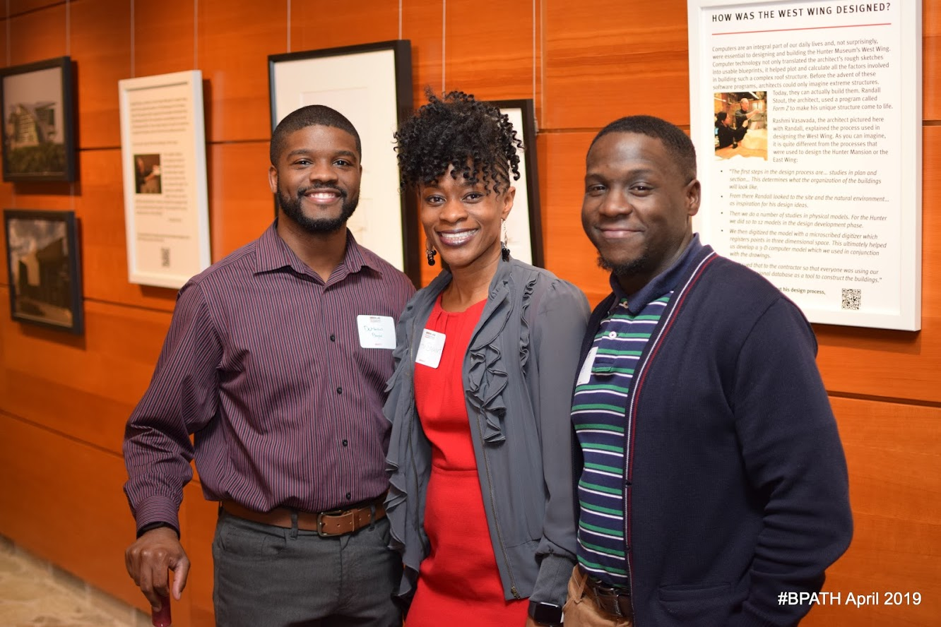 Three attendees of the Black Professionals at the Hunter event posed in front of the wall that depicts the history of the museum.