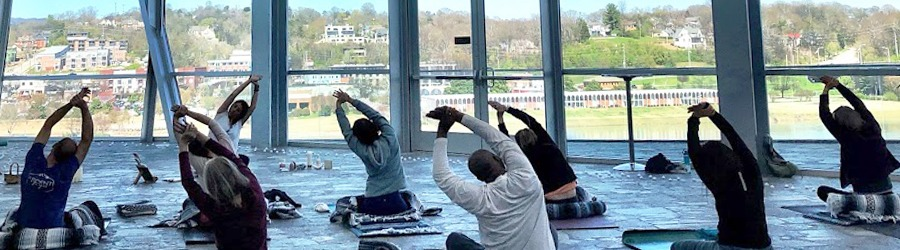 Group of people in the Hunter museum lobby seated on yoga mats stretching to the side with their arms above their heads. An instructor sits at the front of the room.