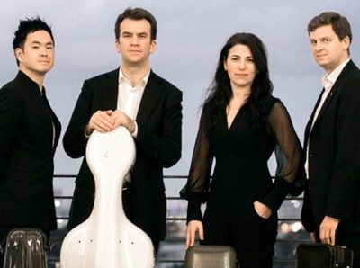 Performers of String Theory wearing black posed with their instruments in cases.