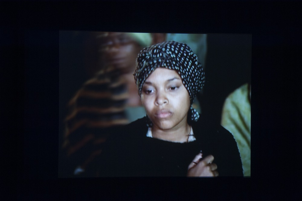 Snapshot from a video on a screen of a woman wearing a head wrap and black shawl looking downwards.