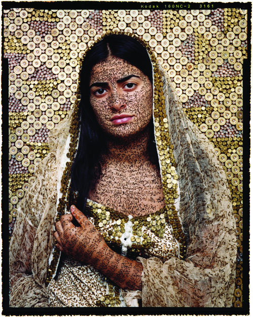 Photo of work by Lalla Essadi, portrait of Arab female with calligraphy written on her skin and bullet shells organized into an ornate pattern on the background.