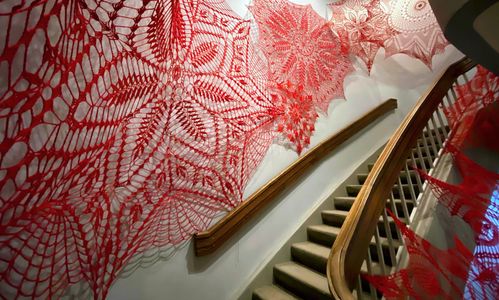 Large red crocheted doilies hung on a wall.
