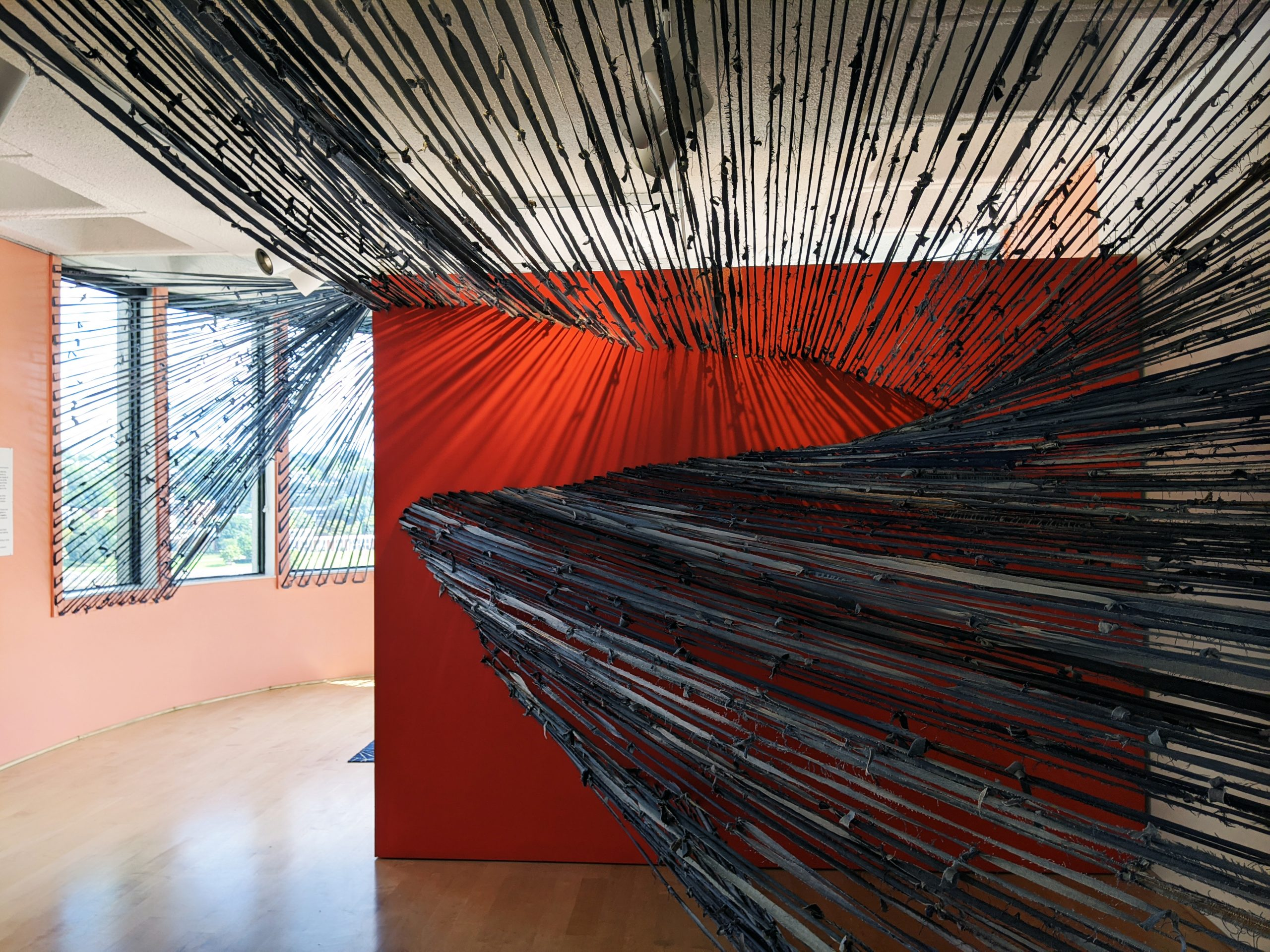 Strips of denim attached to two walls stretched across a room.