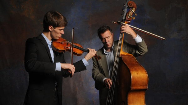 Two men play string instruments.