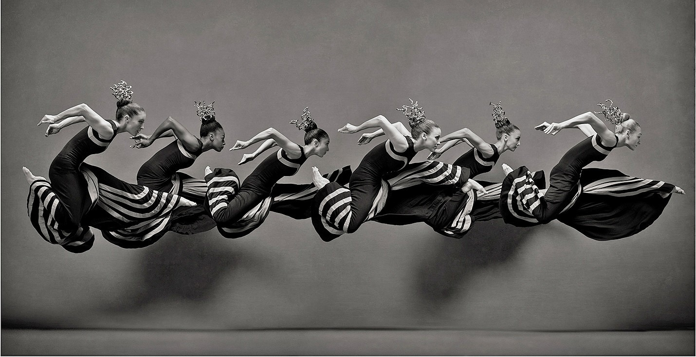 Professional photo of six dancers in the air wearing black and white dresses. This image is included in the Power, Passion, and POSE exhibit.