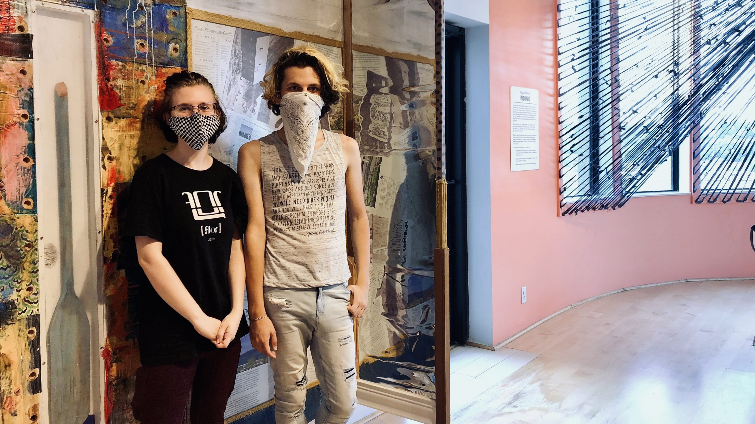 Two teens stand in front of colorful collage on the wall. They are wearing face masks.